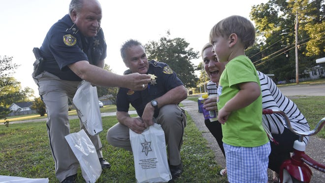 Deputies Bobby Wyche and Joey Raborn hand Tyler Suart a toy badge while at one of the National Night Out locations on Ockley drive in Shreveport.