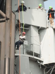Alexis 'Lexi' Keil, a volunteer firefighter with the Fairmount Engine Company No. 2 of Norristown, Pennsylvania, rappels from an upper deck of the Battleship New Jersey as she takes part in NSR Solutions LLC and Med-Tech's Confined Space Training classes Friday.