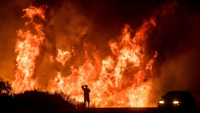 A motorists on Highway 101 watches flames from the Thomas fire leap above the roadway north of Ventura, Calif., on Dec. 6, 2017.