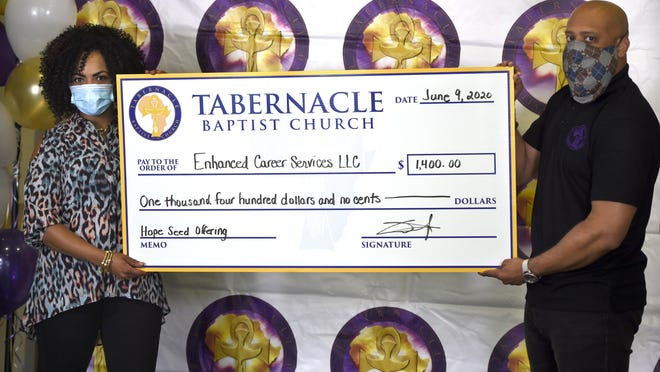Priscilla Gary, founder and owner of Enhanced Career Services, accepts a check from Rev. Dr. Charles E. Goodman, Jr., pastor of Tabernacle Baptist Church. Tabernacle is donating $1,400 to 40 African-American owned businesses in Augusta, after raising almost $56,000 through the church's annual Hope Seed Offering.
