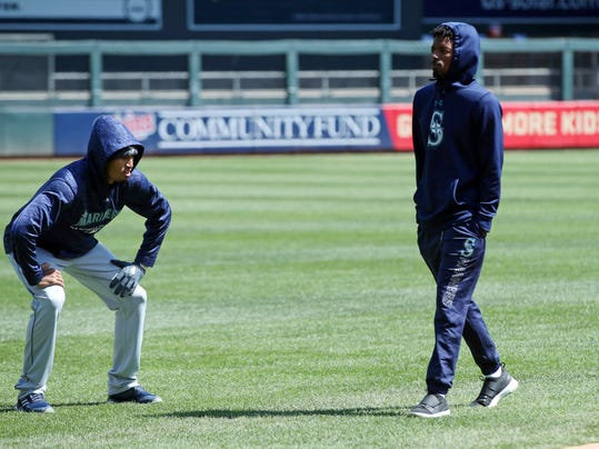 Seattle Mariners' Dee Gordon, right, warms up prior to the Minnesota Twins home opener baseball game Thursday, April 5, 2018, in Minneapolis. Temperatures were in the mid-30's. (AP Photo/Jim Mone)