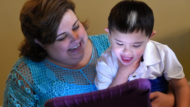 Robyn Schueler is excited as her son, Isaac, works a problem correctly during lessons at home. Schueler is the mother of two children with Down syndrome. She recently left her church after being told that her children wouldn't be able to participate in certain activities because of their disabilities. She has now joined a new church in the Nashville area that is developing a special-needs ministry.