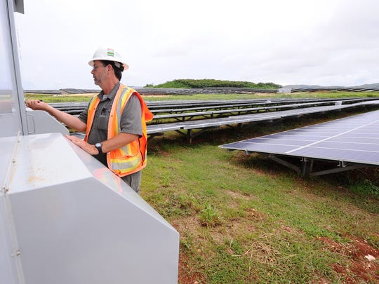 Bill Alexander, nrg Renew project manager, unlocks a building housing power inverters at the company's Dandan Solar Facility on Friday, Aug. 14. The solar plant uses over 120,000 solar voltaic panels to convert the sunlight into a little more than 25 megawatts of power to supply to the Guam Power Authority.