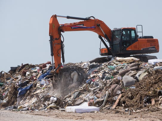 An excavator moves debris at a transfer location in