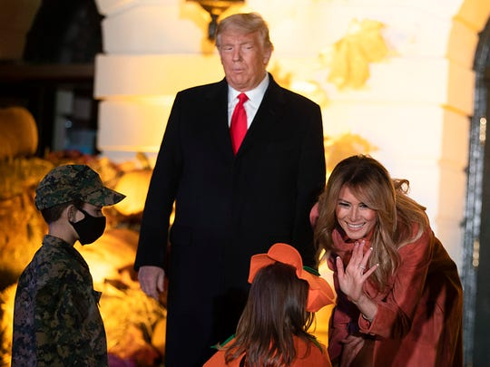 President Donald Trump and first lady Melania Trump greet guests for Halloween festivities on the south lawn of the White House on Sunday.