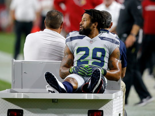 File - In this Sept. 30, 2018, file photo, Seattle Seahawks defensive back Earl Thomas (29) leaves the field after breaking his leg against the Arizona Cardinals during the second half of an NFL football game in Glendale, Ariz. Though the league's biggest stars receive hefty signing bonuses, the push for more guaranteed money across the life of contracts has slowly picked up steam over the past few seasons. The contract holdouts by Le'Veon Bell and Thomas during this season put the issue into vivid focus. (AP Photo/Ross D. Franklin, File)