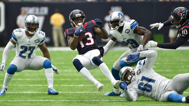 Houston Texans receiver Braxton Miller is tripped up by Detroit Lions defender Kerry Hyder (61) as Glover Quin (27) and Johnson Bademosi (29) look on Sunday, Oct. 30, 2016, in Houston.