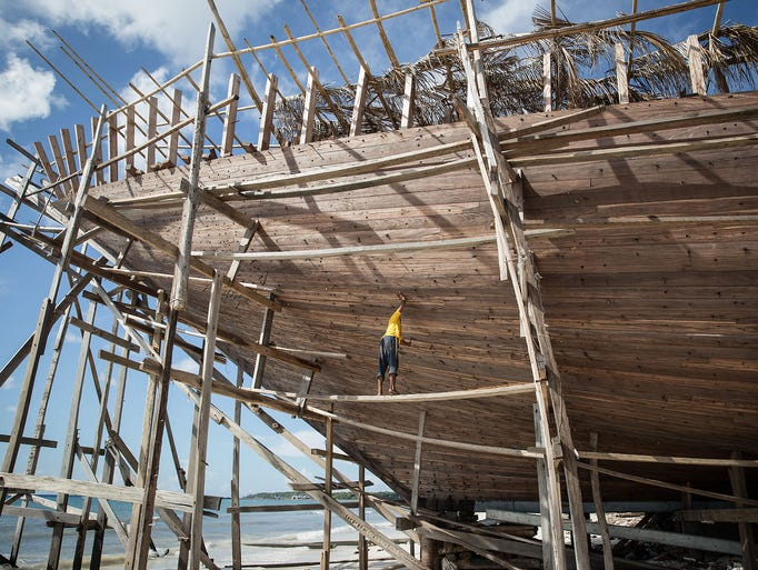 A worker checks the hull of a phinisi, a traditional two-masted sailing ship, at Tanjung Bira Beach on May 2 in Bulukumba, Indonesia. The sailing ship is a masterpiece of traditional design created by the Buginese people. According to the ancient I La Galigo manuscript, the phinisi has sailed the seas since the 14th century.