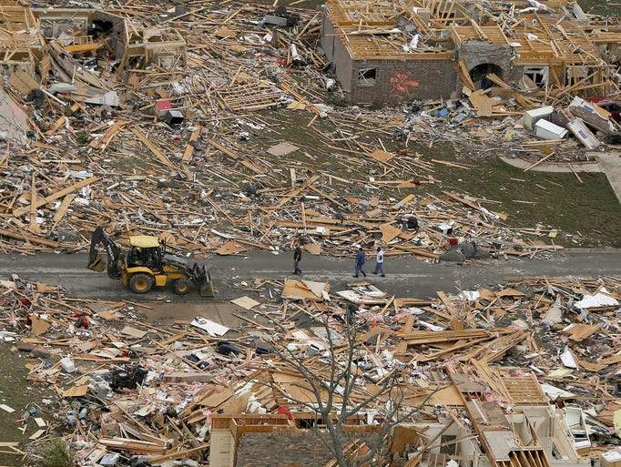 People walk between homes destroyed by a tornado on April 28 in Mayflower, Ark. At least 18 people were killed when a storm system ripped through several states on April 27.