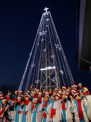 South Korean Christians sing a Christmas song in front of a 100-foot-tall (30-meter-tall) steel Christmas tree that would be visible North Koreans living near the Demilitarized Zone dividing the two Koreas at the western mountain peak known as Aegibong in Gimpo, South Korea, Tuesday, Dec. 21, 2010.