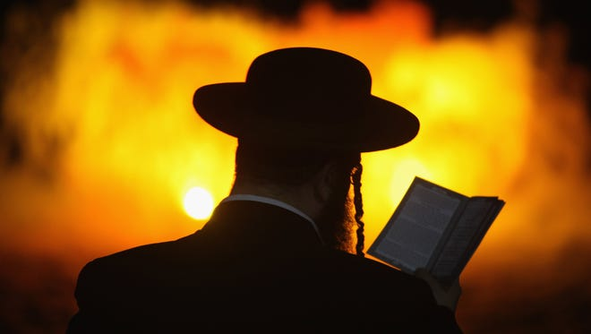 An ultra-Orthodox Jew is silhouetted against a floodlit fountain as he performs the Tashlich ceremony at the shores of a lake on Sept. 24, 2009 in Ramat Gan, Israel. Tashlich, which means 'to cast away', is the practice by which Jews go to a flowing body of water and symbolically 'throw away' their sins during the days of repentance between Rosh Hashanah and Yom Kippur.