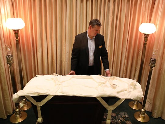 Jack Davenport, owner of Davenport Family Funeral Home and Crematory, moves one of their linen burial shrouds, an option for those seeking a green funeral, at his funeral home on Wednesday, Oct. 30, 2019 in Lake Zurich, Ill. (Stacey Wescott/Chicago Tribune/TNS)