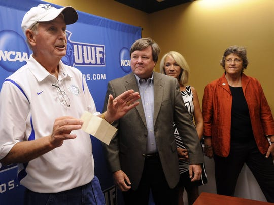 In this file photo, Bob Stinnett, left, the University of West Florida men's basketball coach, proudly accepts a $100,000 check from Joe Ambersley, center, a former University of West Florida athletic director, as Joe's wife, Maggie, and UWF President Judy Bense, right, look on.
