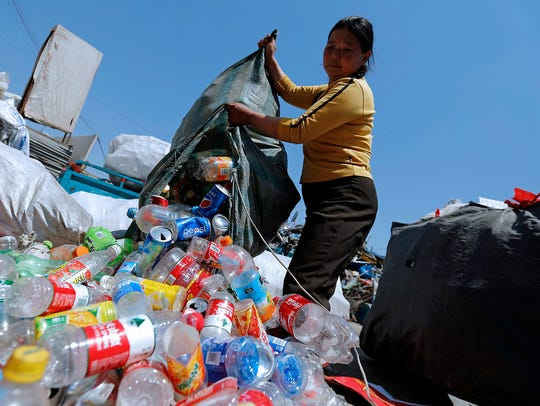 A Chinese migrant worker dumps empty plastic bottles to be sorted out at a recycling center in a rural village outside Beijing. It is one of the largest recycling centers in China, with many migrant workers living and working at the recycling center.