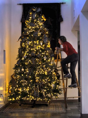 Cynthia Hale on Tuesday climbs a ladder to hang an ornament on a tree at First Central Presbyterian Church. Members were decorating the church in preparation for Advent and the Christmas season.