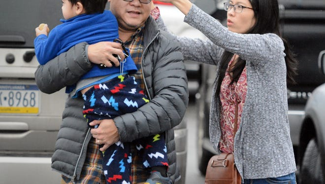 Chau Nguyen puts a cap on her husband Dan who was carrying their son Ocean, 2 1/2, during a drizzle in the Eastern Market parking lot Friday, Jan 12, 2018. They live in Spring Garden Township. Friday's rain could turn to snow and sleet with colder temperatures coming in the region. Bill Kalina photo