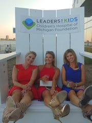 Shelly Johnston, left, Stephanie Bockart, and Kate Kesner chill in the big chair at the Summer Recess event.