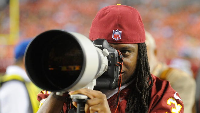 Washington Redskins strong safety Brandon Meriweather (31) looks through a photographer's camera and telephoto lens during the second half of an NFL preseason football game against the Cleveland Browns Monday, Aug. 18, 2014, in Landover, Md.