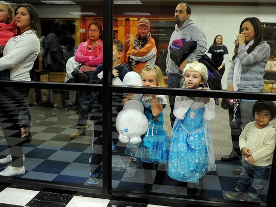 Frozen fans peer through the windows to get a glimpse of characters from the movie Frozen before getting their photos taken with them as a part of Christmas at the Western Mall in 2014.
