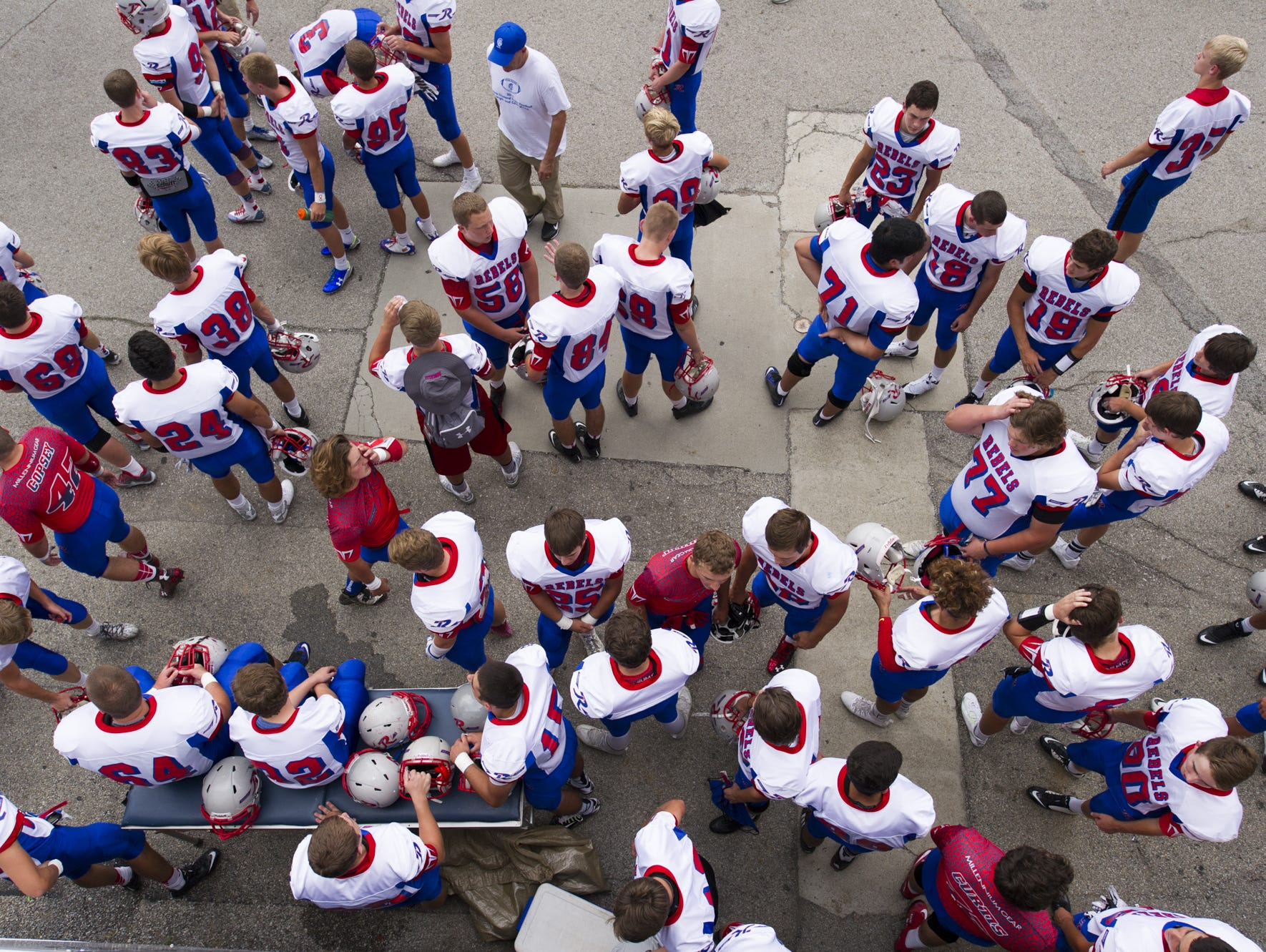 The Roncalli team mingles outside the locker room as they await news of an approaching storm's effect on their game vs. Bishop Chatard. It was eventually postponed to Saturday at 8 p.m.