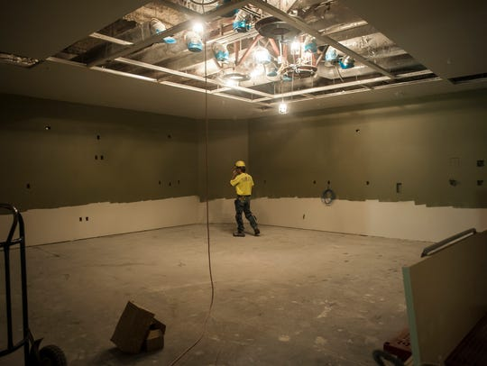 A worker checks the walls during construction on the