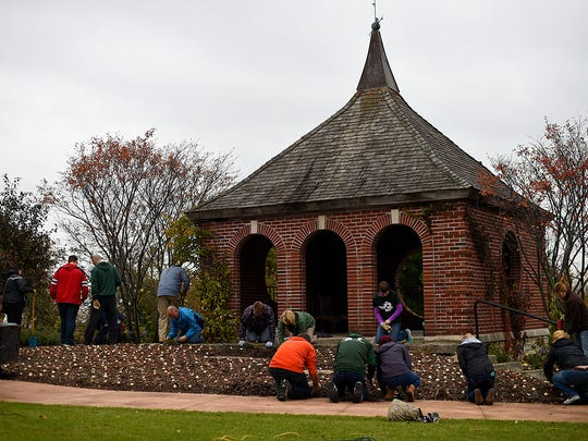 UW-Green Bay students and employees help plant thousands of spring bulbs as part of their Make A Difference Day activities Friday at the Green Bay Botanical Garden.