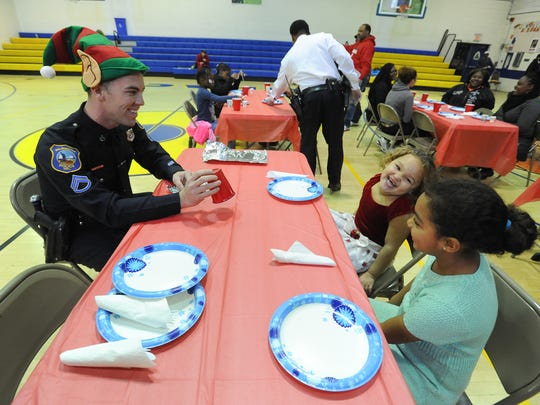 Former Wilmington Police Senior Cpl.  Thomas Oliver shows children a magic trick departments first ever breakfast for the youth at West Center City's Hicks Anderson Center in 2015.