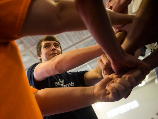 Evan Brown works with teammates and they untangle themselves during the Human Knot exercise on Dec. 21, 2015 at New Oxford High School.