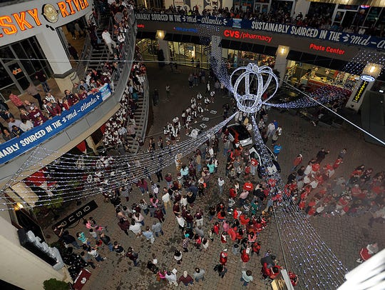 Mississippi State Bulldogs fans on the left and NC State Wolfpack fans on the right during the Belk Bowl Fan Central celebration at the EpiCentre in Charlotte, NC.