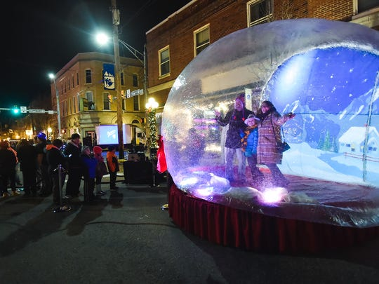 Matt, Sarah and Trudy Wilkin stand inside an inflatable snow globe to take family photos in downtown Shippensburg, Pa. on Dec. 31, 2015. All the festivities downtown for New Years Eve were free.