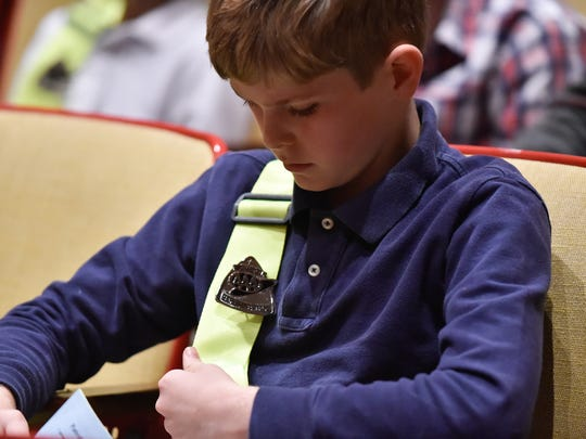 Mispillion elementary school 5th grade student Liam Dennehy looks at his new safety patrol badge and belt after being sworn in a new AAA Safety Patrol member during a ceremony at Milford Senior High School.