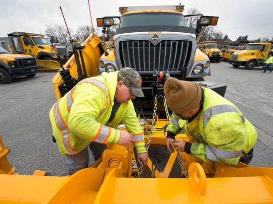 Jim Huggins, left, and Rich Emenheiser install a new plow on a truck at PennDOT in Manchester Township preparing for snow to start Friday night.