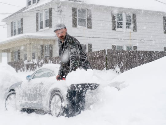 Jesse Kin tries to clear snow away from his Audi during