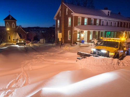 A plow truck tries to get to another plow truck stuck in the snow in Manchester Township at sunrise Sunday.