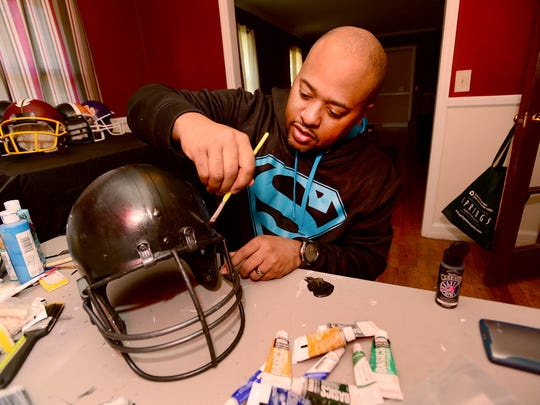 Shawn Russell, owner of HARDHEDZ Custom Helmet, half paints football helmets out of his Greenville home on Friday, January 29, 2016.