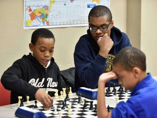 Johnny Means, center watches as Kasie Dorsey, 11, left