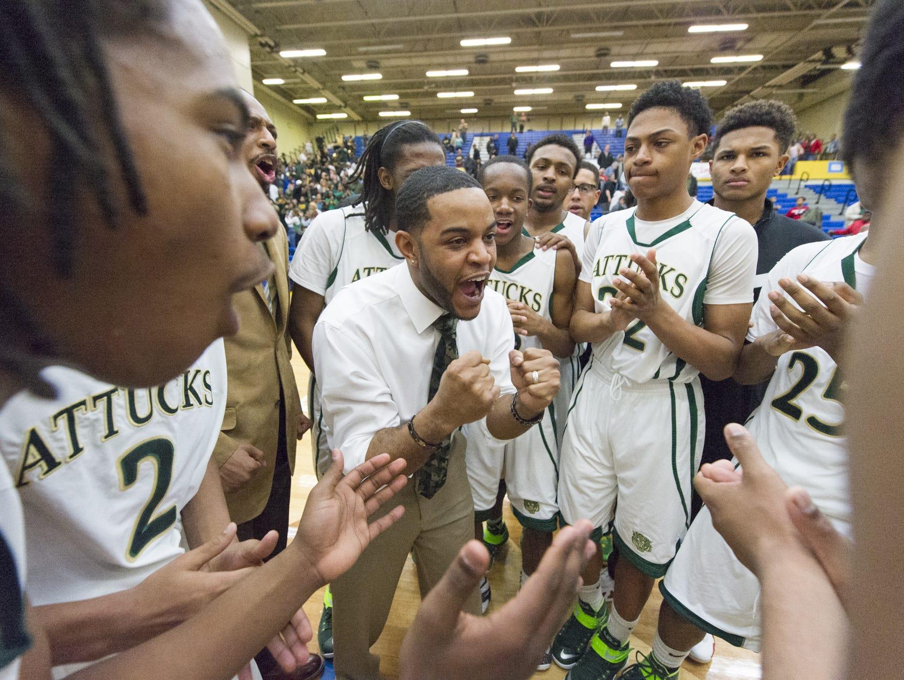 FILE – Former Attucks coach Phillip Washington (center) celebrates the a Class 2A regional win on March 14, 2015.