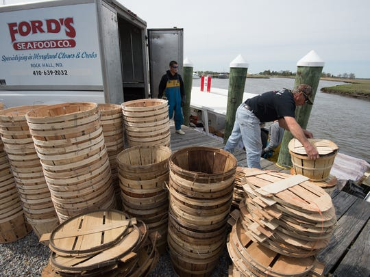 Lee Thomas, right, owner and captain of the Migrator helps to unload 80 bushels of crab outside of Sambo's Tavern seafood restaurant in Leipsic.