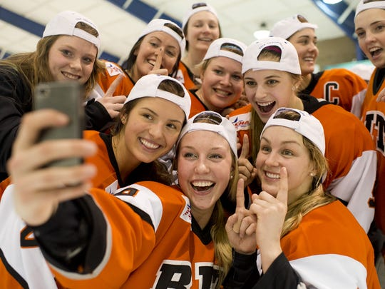 The RIT Tigers women's hockey team celebrates with RIT fans after winning the CHA Championship in 2014.