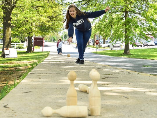 Leah Staver rolls a wooden ball down a side walk as