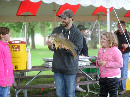 Dan Crossman of Fond du Lac shows off his 5.03 pound Sheephead to Madison Shaw (left) and Isabell Crossman (right), during the family fishing tournament at Walleye Weekend Saturday June 13, 2015.