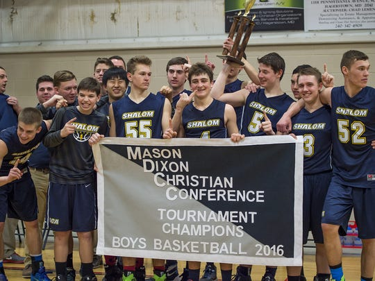 Shalom Christian Academy boys basketball team pose together holding a trophy after winning the Mason-Dixon Christian Confrence basketball championship in February.