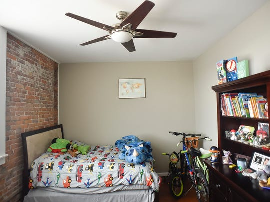 A stuffed triceratops keeps watch at the foot of Logan Wertman's bed at Flyingfish Lofts in downtown Marion.