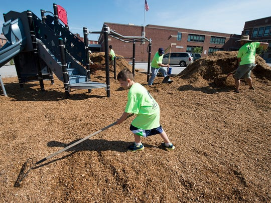 Ben Cotton, age 8, spreads mulch with other church