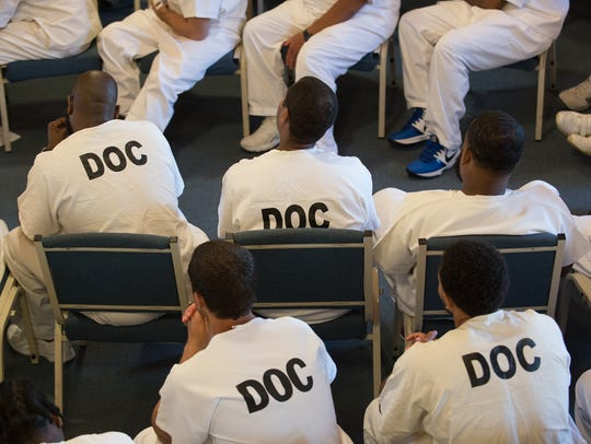 Inmates at the Sussex Correctional Institution listen