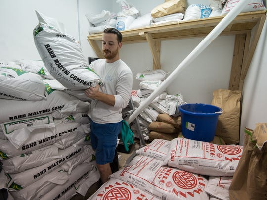 Brewmaster Andrew Harton grabs a bag of barley for brewing beer at Big Oyster Brewery in Rehoboth.