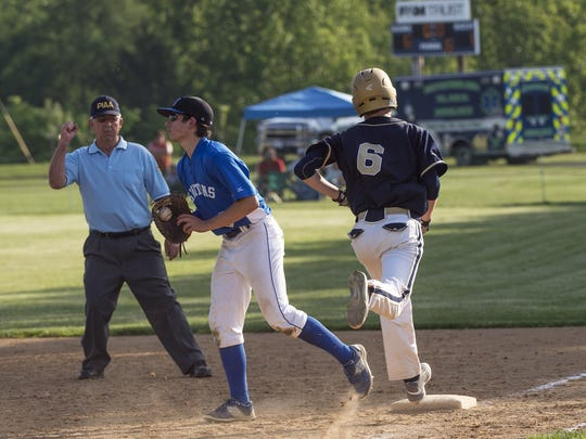 An umpire makes an out call at first base during a District 5 Class A quarterfinal baseball playoff game between Forbes Road and McConnellsburg in May.