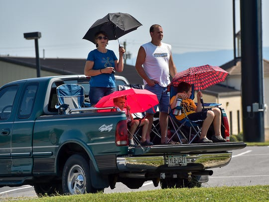 A family sits in the back of a pickup truck in a parking lot and watch as the semi trucks drive down U.S. 30  for the Make A Wish Convoy on Saturday, August 20, 2016.