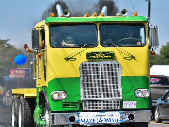 A family inside a semi truck wave to people as they ride down U.S. 30 for the Make A Wish Convoy on Saturday, August 20, 2016.