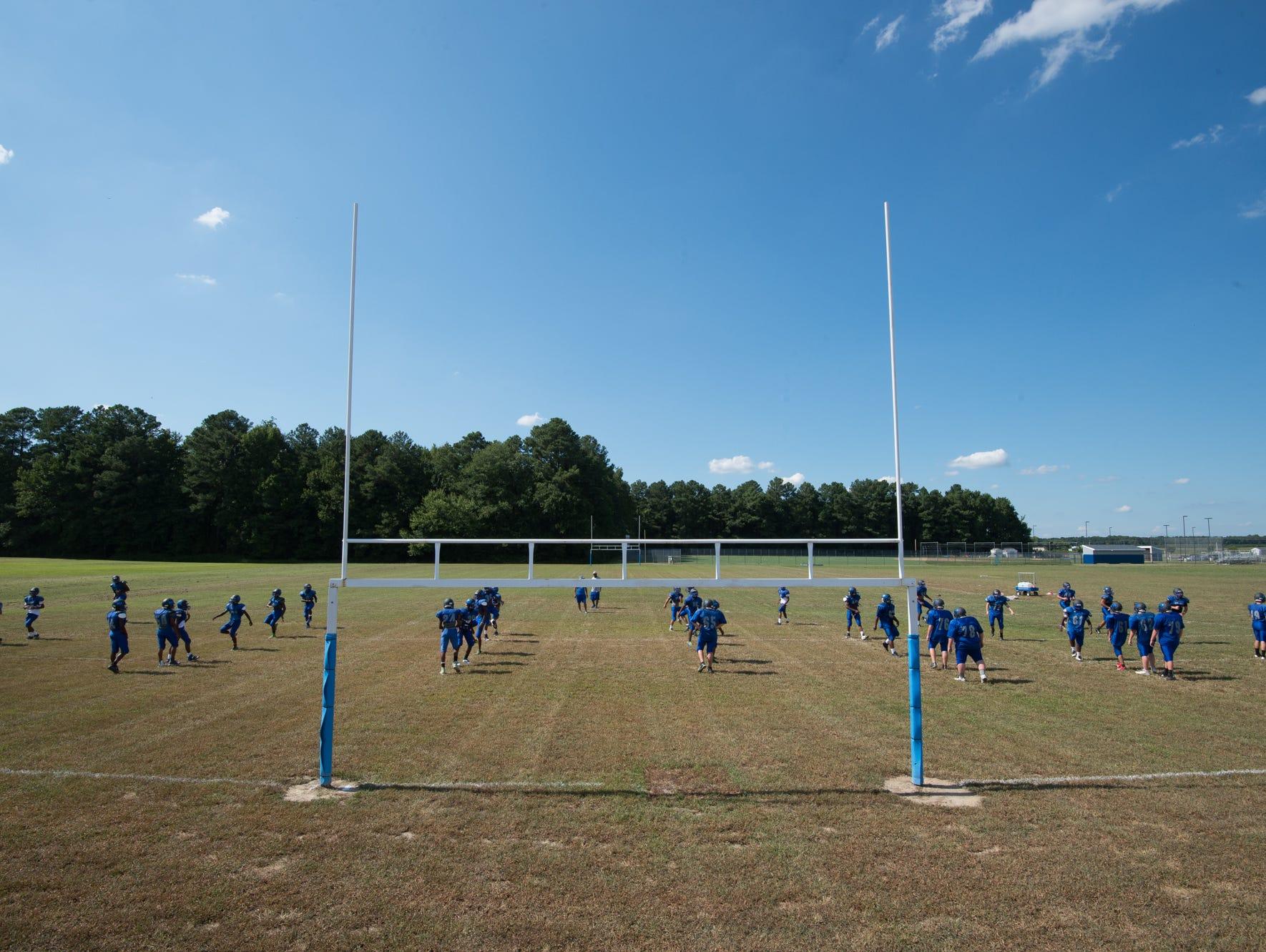 Woodbridge High School football team stretches before practice.